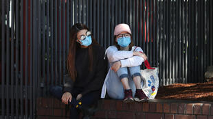 Women wear protective face masks amidst fears of the coronavirus disease (COVID-19) in Sydney, Australia, March 18, 2020.