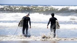 Christopher Hawley (izq) y su amigo Bernard Yin, listos para hacer surf en la playa californiana de Venice (EEUU) el primer día de su reapertura, el 13 de mayo de 2020