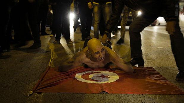 """""""Vive la Tunisie, Vive Nidda Tounès, Vive Bajbouj (surnom de BCE en Tunisie) !"""", crie un homme torse nu en s'allongeant sur le drapeau rouge à croissant blanc."""