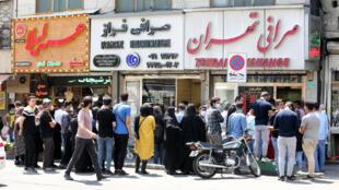 Decenas de iraníes con mascarilla pero sin respetar la distancia social hacen fila fuera de unas oficinas de cambio de Teherán el 9 de mayo de 2020