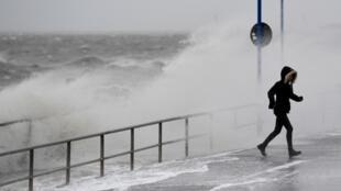 Una niña camina en el puerto mientras la tormenta Sabine golpea la costa de Dagebuell en el Mar del Norte, Alemania, el 9 de febrero de 2020.