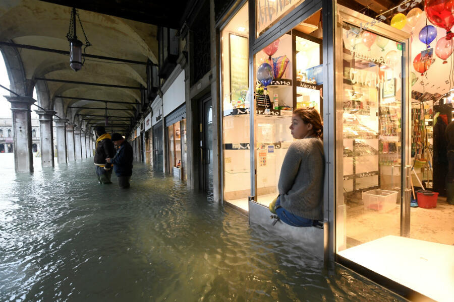 A woman looks out from a shop upon the flooded St. Mark's Square at hight tide in Venice on November 15, 2019.