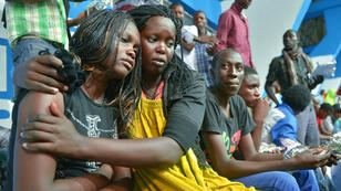 A survivor of an attack by by al Shabaab on a university campus in Garissa, northern Kenya is comforted by a colleague after arriving in Nairobi on April 4, 2015
