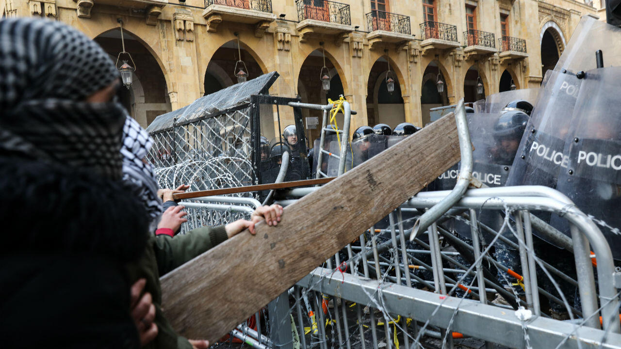 Protesters use a road sign to ram barricades near the parliament in Beirut on January 18, 2020.