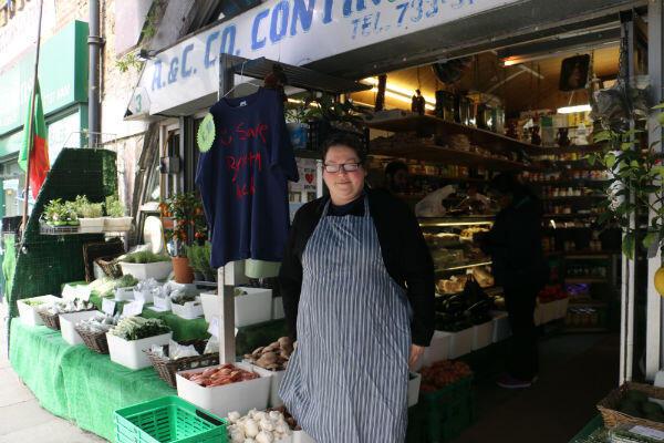 """Anabella Cardoso, devant son épicerie, sous les arches du chemin de fer de Brixton. À côté d'elle pend un tee-shirt """"Sauvez les arches de Brixton""""."""