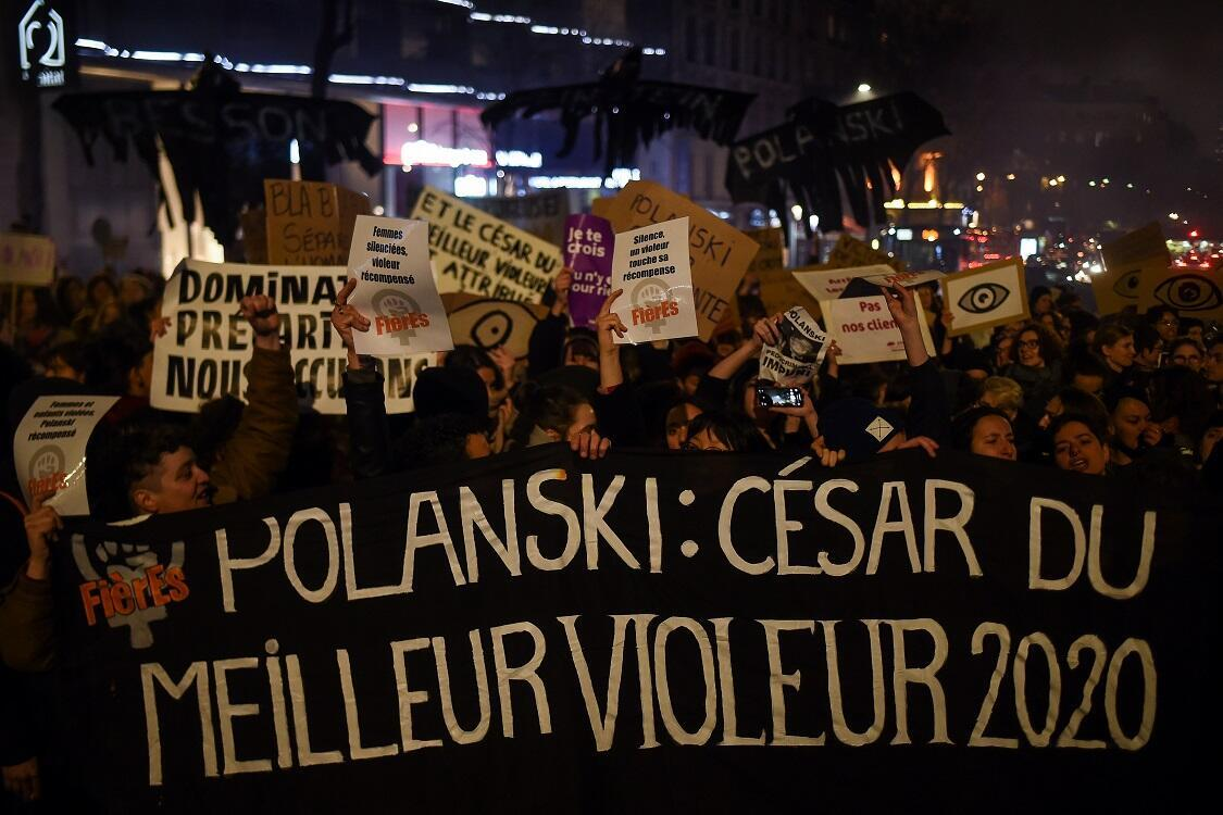 """Feminist activists hold a banner reading """"Polanski: Best rapist 2020 award"""" during a demonstration outside the Salle Pleyel in Paris as guests arrive for the 45th edition of the César Film Awards ceremony on February 28, 2020."""