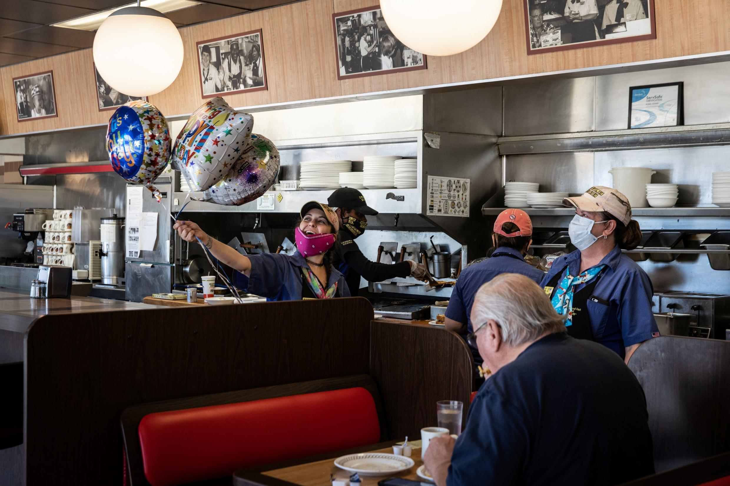 A staff member holding balloons at a Waffle House in Madison, Georgia, USA on April 27, 2020.