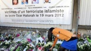 باقات ورود امام المدرسة اليهودية التي قتل محمد مراح ثلاثة من تلاميذها مع مدرسهم في 11 آذار/مارس 2012