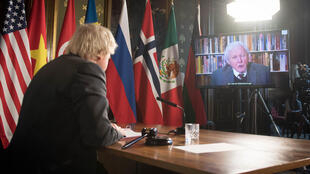 Britain's Prime Minister Boris Johnson watches a video address by Sir David Attenborough as he chairs a virtual session of the UN Security Council on climate and security