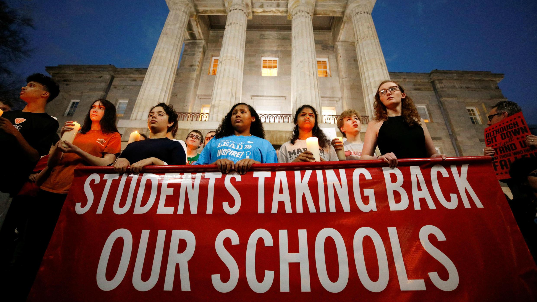 Estudiantes sostienen velas en memoria de las víctimas del tiroteo frente al edificio del Capitolio del Estado de Carolina del Norte durante una marcha por leyes de armas más seguras.