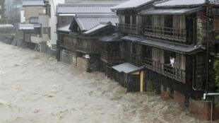 Des hommes regardent la rivière Isuzu en crue à cause des fortes pluies causées par le typhon Hagibis à Ise, au Japon, le 12 octobre 2019.