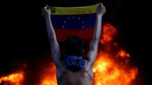 Un manifestante sostiene la bandera nacional de Venezuela frente a un incendio en la entrada de la Corte Suprema de Justicia durante una manifestación contra el presidente Nicolás Maduro (Caracas, Venezuela - 12 de junio de 2017).