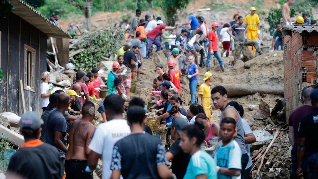 """Vista este miércoles de habitantes y bomberos buscando a los desaparecidos tras el derrumbe en el """"Morro do Macaco Molhado"""", en Guarujá (Brasil)."""