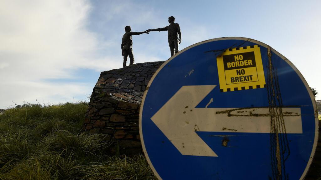 Se ve una etiqueta adhesiva 'No Border, No Brexit ' en una señal de tráfico frente a la estatua de la Paz titulada 'Hands Across the Divide' en Londonderry, Irlanda del Norte, el 22 de enero de 2019.