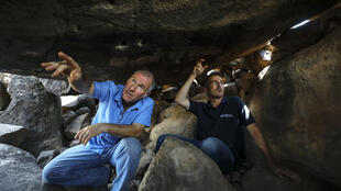 Uri Berger (R), a regional archaeologist for the Israel Antiquities Authority, and Gonen Sharon, a professor of archaeology at northern Israel's Tel-Hai college, display ancient engravings inside a dolmen