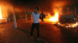 Un homme armé lève son fusil lors de l'attaque du consulat américian de Benghazi, le 11 septembre 2012.