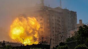 صورة للحظة استهداف الجيش الإسرائيلي المبنى الذي يحوي مكاتب وسائل إعلام عالمية وتدميره في 15 أيار/مايو 2021 في قطاع غزة