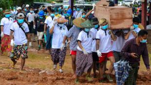 Los voluntarios llevan un ataúd que contiene el cuerpo de una víctima después de un deslizamiento de tierra en un sitio minero en Hpakant, ciudad del estado de Kachin, Myanmar, 3 de julio de 2020. REUTERS