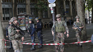 In this file photo from June 6, 2017, policemen and soldiers block access to Notre-Dame Cathedral after a man with a hammer attacked policemen who were patrolling the esplanade in front of the famous monument in Paris, France.