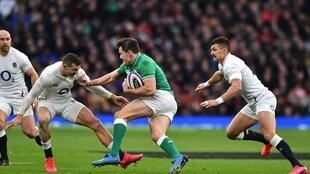 Ireland's wing Jacob Stockdale (C) is tackled by England's wing Jonny May (L) during the Six Nations international rugby union match between England and Ireland at the Twickenham, west London, on February 23, 2020