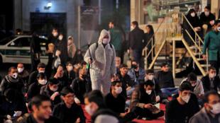 إيرانيون يرتدون أقنعة واقية أمام مسجد في طهران في 13 أيار/مايو 2020