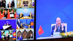 El primer ministro de Vietnam, Nguyen Xuan Phuc(dcha), aplaude junto a sus homólogos de los otros países firmantes del acuerdo comercial, durante la cumbre virtual de los países del foro del sureste asiático ASEAN, el 15 de noviembre en Hanói