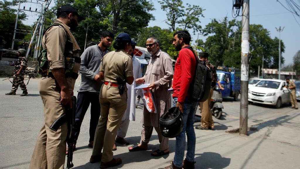 Un oficial de policía indio revisa los documentos de personas en una carretera durante las restricciones en Srinagar, Cachemira, el 6 de agosto de 2019.