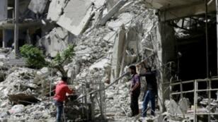 سوريون يشربون المياه في دوما في 16 نيسان/أبريل خلال جولة نظمتها السلطات بعد إعلان استعادة منطقة الغوطة الشرقية بالكامل.