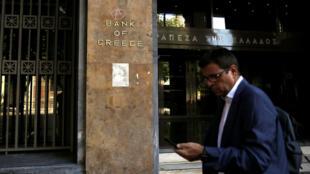 Un ciudadano griego pasa frente a la fachada de la sede central del Banco de Grecia, uno de los principales actores de la crisis económica helena, en Atenas, Grecia, el 20 de agosto de 2018.