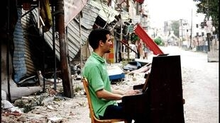 Ayham Ahmed au piano dans le camp de Yarmouk