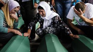 Des familles de victimes de Srebrenica se recueillent sur les cercueils de leurs proches qui seront réenterrés pour le 20e anniversaire du massacre.