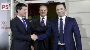 Manuel Valls et Benoît Hamon se serrent la main sous les yeux du premier secrétaire du Parti socialiste Jean-Christophe Cambadélis, dimanche 29 janvier 2017, à Paris.