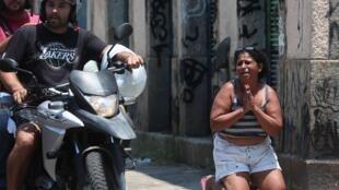 Una mujer se arrodilla en medio de un operativo policial que resultó en un tiroteo este viernes 8 de febrero, en Río de Janeiro (Brasil).