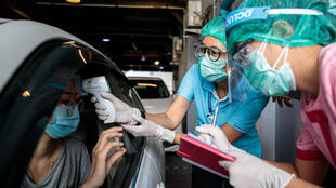 طاقم طبي يختبر امرأة لمعرفة إن كان مصابة بفيروس كورونا المستجد في مركز اختبار عبر المرور بالسيارة في مستشفى فيبهافادي في بانكوك في 25 آذار/مارس 2020، يشمل الاختبار أخذ مسحة ممن الأنف والحنجرة مع توقع النتائج خلال 5 إلى 7 أيام .