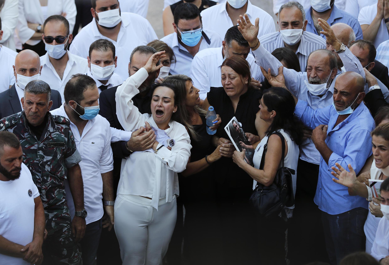 Familiares de tres de diez bomberos que murieron durante la explosión del 4 de agosto que afectó el puerto de Beirut, lloran durante su funeral en Beirut, Líbano, el lunes 17 de agosto de 2020.