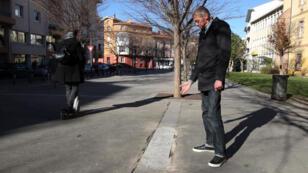 Un membre de l'association Frene66 désigne l'endroit où un banc public a été enlevé à Perpignan.