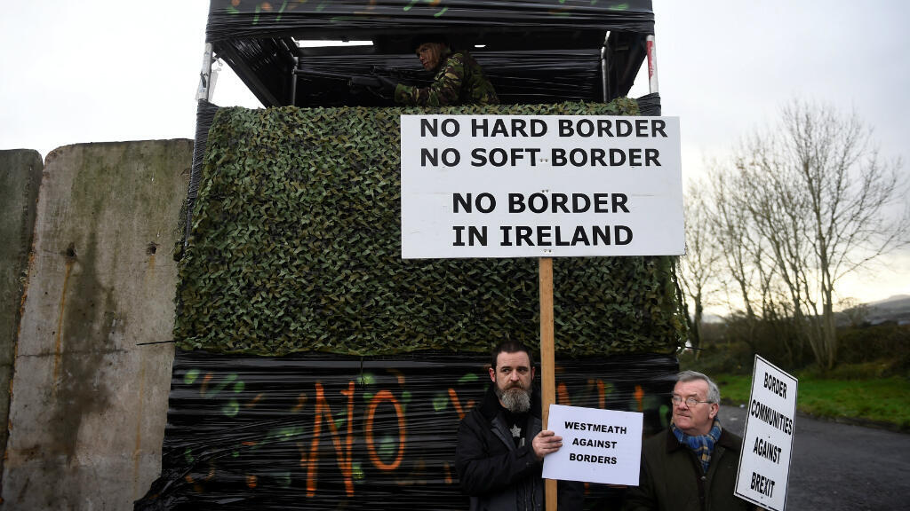 Las personas tienen carteles junto a una barricada fronteriza simulada durante una protesta de activistas contra el Brexit,en Carrickcarnan, Irlanda, el 26 de enero de 2019.