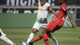 L'attaquant français de Mönchengladbach, Alassane Pléa (g), auteur d'une passe décisive lors de la réception du Bayer Leverkusen, en Bundesliga, le 23 mai 2020
