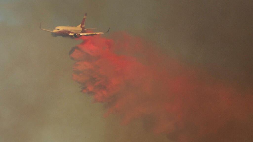 Aviones cisterna lanzan agua para ayudar a los bomberos a contener las llamas de un incendio forestal en las colinas de Canyon Country, al norte de Los Ángeles, California, EE. UU., el 24 de octubre de 2019.