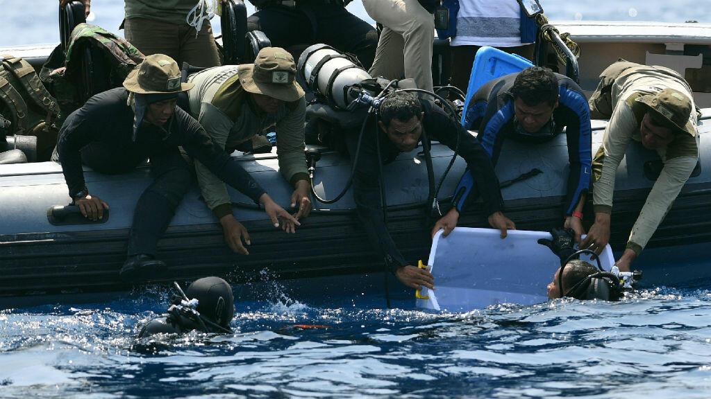 Buzo de la Armada de Indonesia sostiene una de las cajas negras recuperada debajo del agua, tres días después del accidente aereo. Foto tomada el 1 de noviembre.