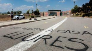 """Un grafiti dice """"los queremos en casa libres"""" en una vista de los accesos al centro penitenciario de Lledoners, en Sant Joan de Vilatorrada (Barcelona) en donde los lazos amarillos están presentes en todo el camino que conduce hasta la entrada de la prisión y que fueron colocados la pasada noche por los CDR de Sant Joan de Vilatorrada a modo de comité de bienvenida para los exconsellers Oriol Junqueras y Raul Romeva y los dirigentes del independentismo civil Jordi Sánchez y Jordi Cuixart. 3/07/2108"""
