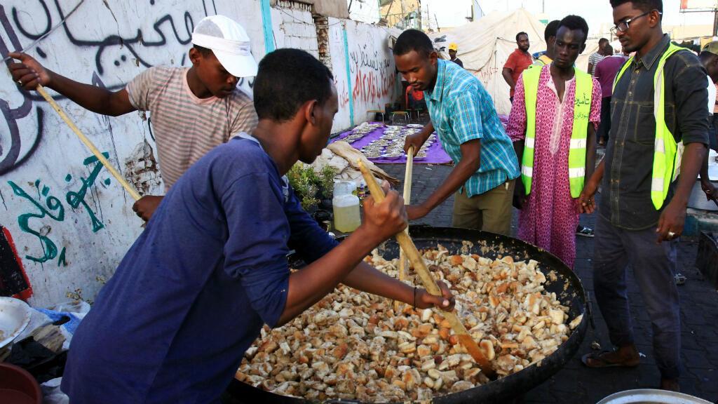 Un grupo de manifestantes sudaneses prepara el iftar, la comida con la que se rompe el ayuno diario en Ramadán, a las afueras del Ministerio de Defensa de Sudán, en Jartum, el lunes 6 de mayo de 2019.