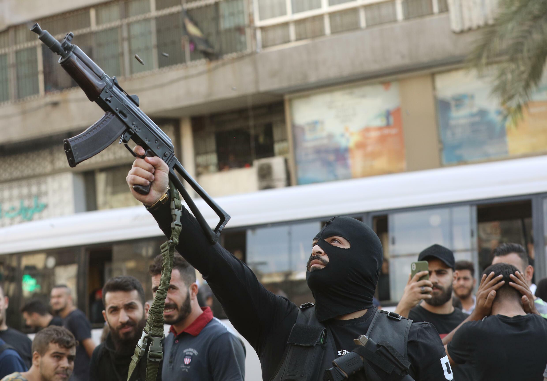 عضو في حزب الله اللبناني يطلق النار من بندقيته خلال جنازة أعضاء في الحزب قتلوا خلال اشتباكات في حي الطيونة بضاحية بيروت الجنوبية في اليوم السابق، في 15 تشرين الأول/أكتوبر 2021