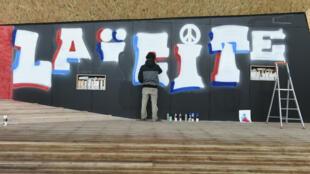 """Un """"street artiste"""" écrit """"laïcité"""" lors de l'inauguration de la Place de la Laïcité, le 9 décembre 2015, à Paris."""