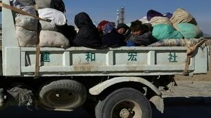 Members of an internally displaced Afghan family sit on a truck as they flee from Jaghori district to escape ongoing battles between Taliban and Afghan security forces