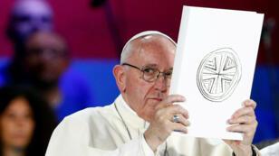 El Papa Francisco sostiene el Libro de los Evangelios cuando se encuentra con jóvenes italianos en el antiguo Circo Massimo en Roma, Italia, el 11 de agosto de 2018.