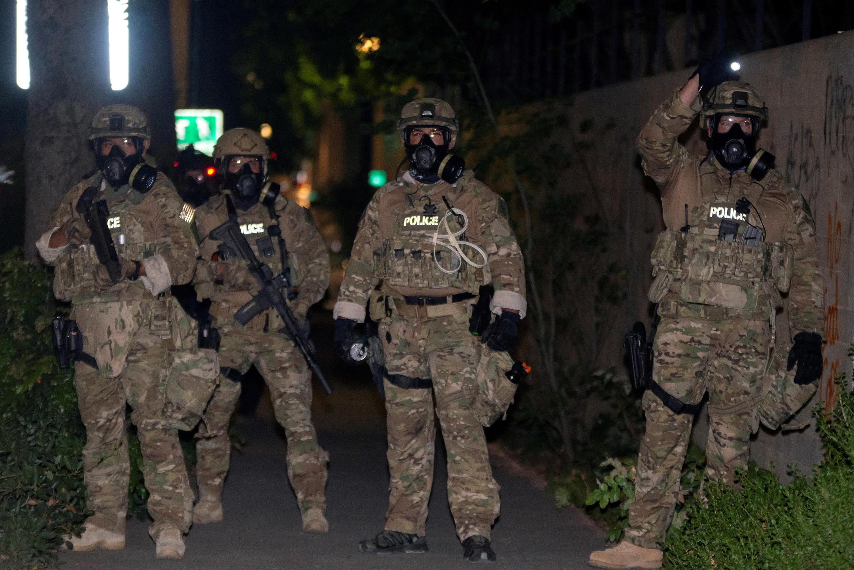 Des agents des forces de l'ordre fédérales, déployés en vertu du nouveau décret de l'administration Trump, font face à des manifestants antiracistes à Portland, Oregon, aux États-Unis, le 17 juillet 2020.