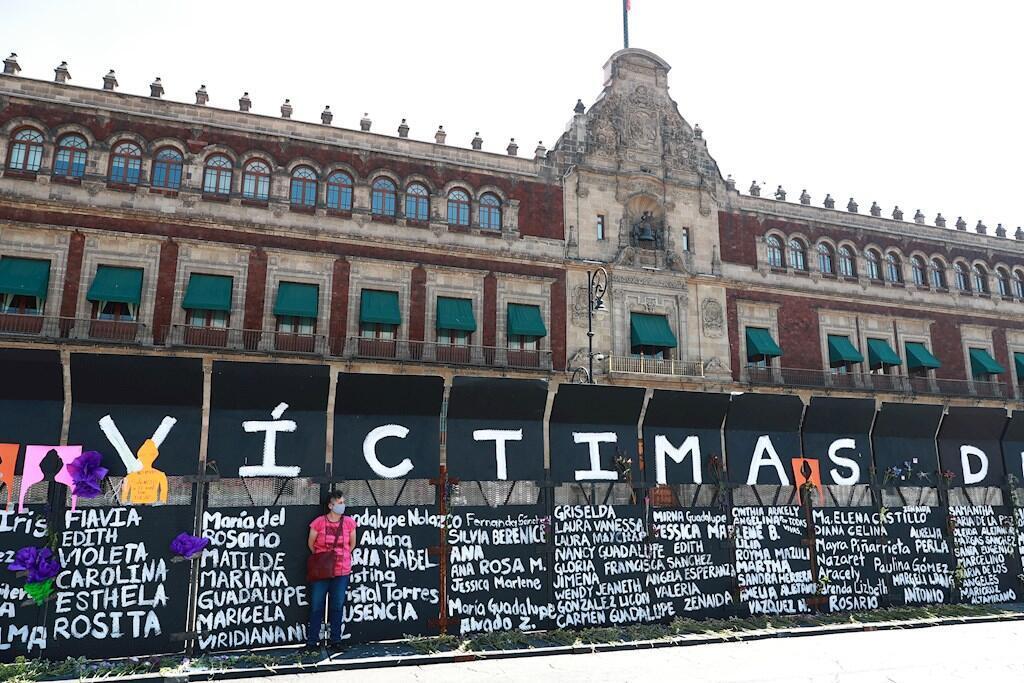 Mujeres activistas instalan carteles con nombres de víctimas por feminicidios en cercos metálicos instalados por el gobierno capitalino, en una protesta contra los feminicidios, en Ciudad de México, México.