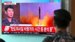 مواطن كوري جنوبي يشاهد على شاشة تلفزيون في محطة قطارات في سيول في 4 تموز/يوليو 2017 صورا أرشيفية لإطلاق كوريا الشمالية صاروخا.