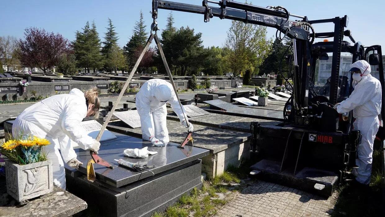 عمال البلدية يرتدون ملابس واقية لدفن ضحايا فيروس كورونا في مقبرة السلفادور في فيتوريا بإسبانيا، 27 مارس/آذار 2020